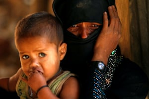 A Rohingya refugee cries next to her son outside a temporary mosque at the Kutupalong refugee camp.