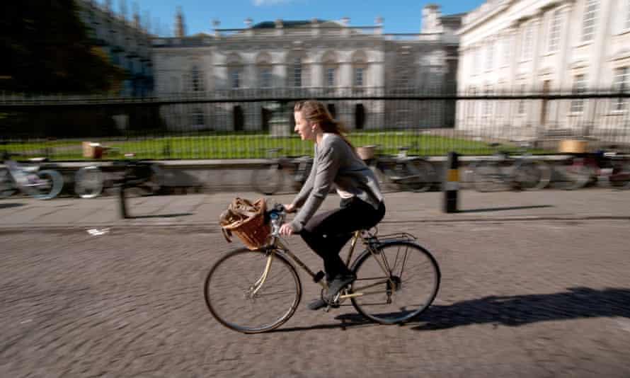 A woman cycles past the Senate House, Cambridge