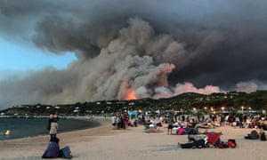 People who have been evacuated due to forest fires find refuge on the beach and look at a fire burning the forest in Bormes-les-Mimosas