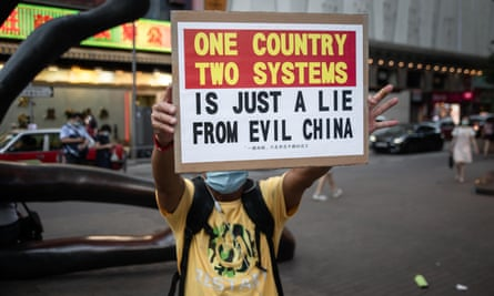 A protester in Hong Kong holds a placard on Sunday at a march that disrupted by riot police.