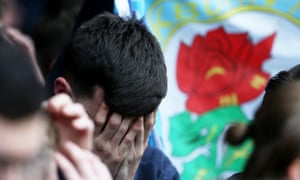 A Blackburn Rovers fan holds his head in his hands as news filters through of the club's relegation