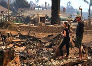 Jade Reily and neighbour Grant Lemaster look at the ruins of their homes destroyed by the Thomas fire