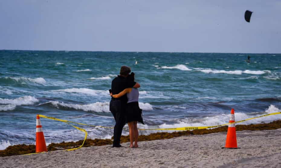 A couple hugs near the scene of the collapse in Surfside.