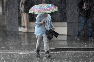 Heavy rain falls in Sydney's CBD Friday morning