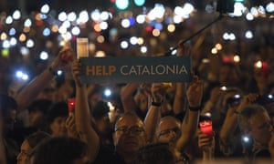 A man holds a placard during candle-lit demonstration in Barcelona