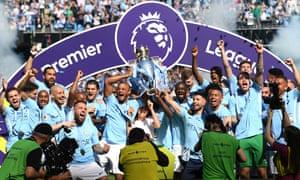 Manchester City players lift the Premier League title.