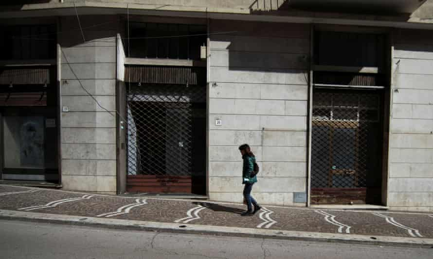 A woman walks past a closed shop in the red zone town of Frosinone, central Italy