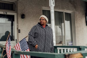 Cathy Morse stands on her porch at her home in Chester, Pennsylvania. Though she would like to move, she can't because it's her mother's home and her mother is elderly and unable to leave.