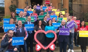 Crowds of campaigners on steps holding up signs reading: 'Equal'
