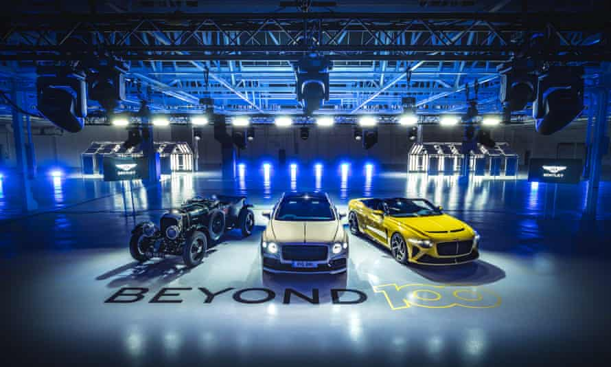 Three Bentley models, from the past, present and near future, in a pool of light in a warehouse