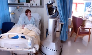A remote control device next to a patient in bed in a surgical ward