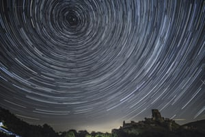 Satellites, planes and comets transit under stars that appear to swirl above Corfe Castle in Dorset