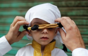 A Muslim man adjusts the headgear of his son during a religious procession to mark Eid-e-Milad-ul-Nabi, the birthday celebrations of prophet Muhammad