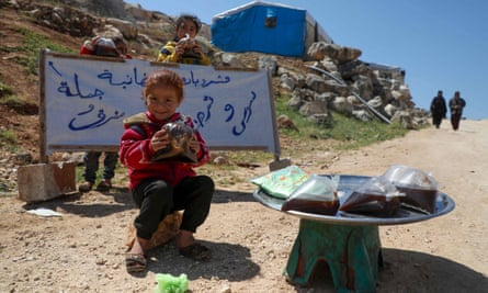 A Syrian girl sells liquorice juice known as Jallab on the roadside near the Bab al-Hawa border crossing