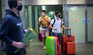 Travellers wearing face masks arrive from Paris to St Pancras Station in London after quarantine restrictions were imposed at 4am on Saturday morning.