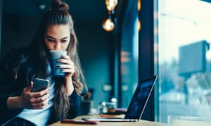 Cute hipster girl with long hair watching interesting video while drinking tasty beverage indoors.Young female student checking notification on smartphone connected to 4G internet in coffee shop