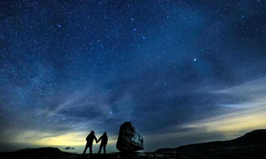 Walkers look up into the night sky above Twistleton Scar in the Yorkshire Dales national park - the largest dark sky reserve in the UK.