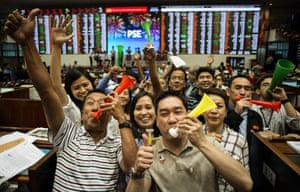 Traders celebrate during the last day of trading at the Philippine Stock Exchange in Manila.