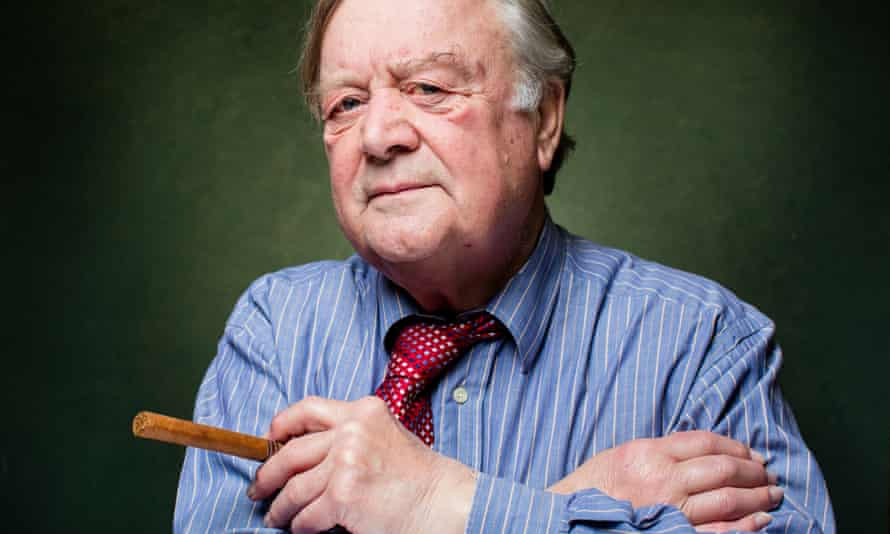 Portrait-style photo of Kenneth Clarke looking directly at camera holding a cigar.