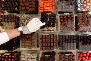 Brussels, BelgiumA vendor selects pralines at Belgian chocolate shop Neuhaus inside the Galeries Royales Saint-Hubert