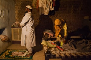 Samsuddil, 41, prays while Najida* puts their three-month-old son to bed in their house in Mewat district on 15 October 2016