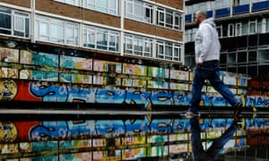 A man passes graffiti near Old Street's 'Silicon Roundabout' technology hub in Shoreditch, east London.