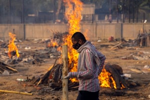 A man walks past burning funeral pyres of people, who died due to the coronavirus disease (COVID-19), at a crematorium ground in New Delhi, April 22, 2021