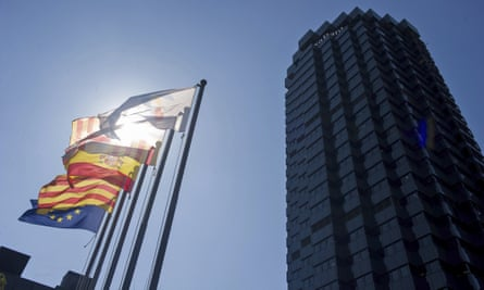 EU, Catalan, and Spanish flags outside Caixabank HQ in Barcelona