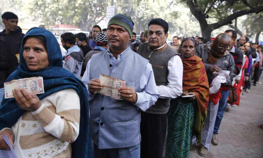 Indian people hold old banknotes as they line up to deposit them outside the Reserve Bank of India in New Delhi.