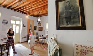 Iro (left) with visitors in Plaka's cultural museum. Elena's great-grandfather is in the photo on the wall.