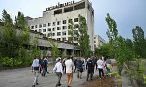 Visitors walk in the ghost city of Pripyat during a tour in the Chernobyl exclusion zone in June.