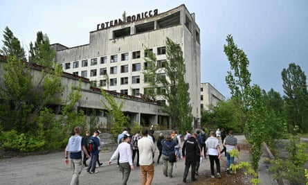 Visitors walk in the ghost city of Pripyat during a tour in the Chernobyl exclusion zone.