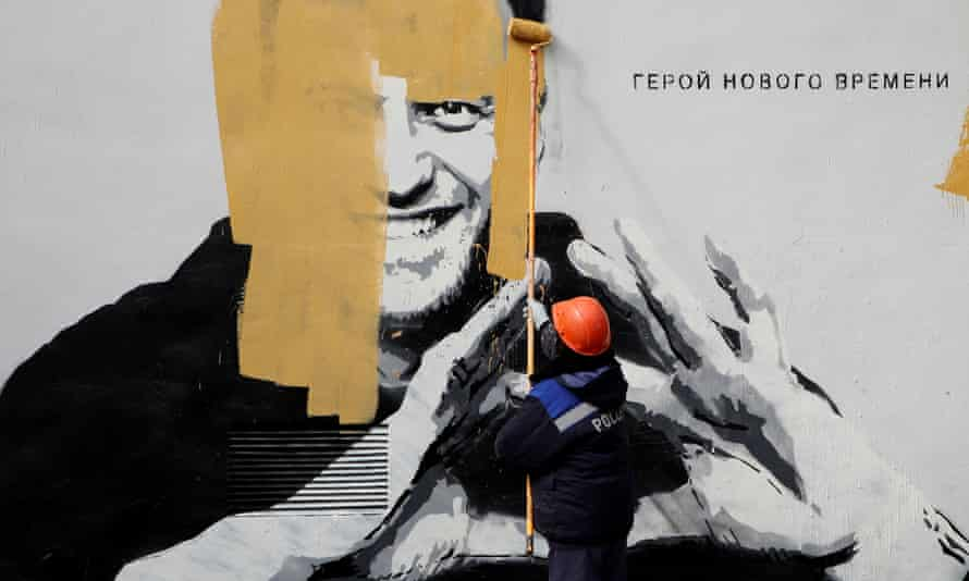 A worker paints over a graffiti depicting Alexei Navalny in Saint Petersburg. Legal aides representing the Navalny movement said they believed the court was attempting to fast-track the hearing.