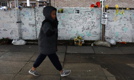 A child walks past a wall of tributes to Grenfell victims