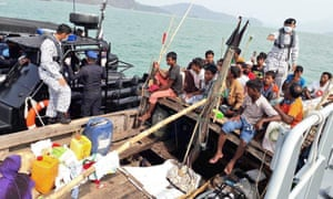 Malaysian navy officers detain a boat carrying Rohingya migrants off Langkawi