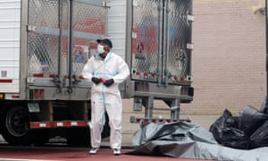 A dressed in a hazmat suit and face mask stands in front of the doors of two big refrigerated trucks outside a funeral home in Brooklyn, New York.