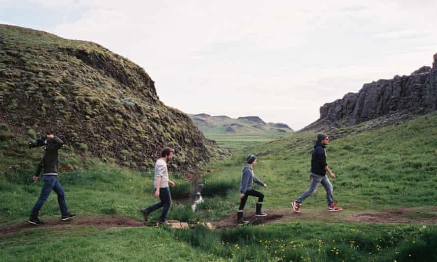 Four people walking in front of sharp rocks