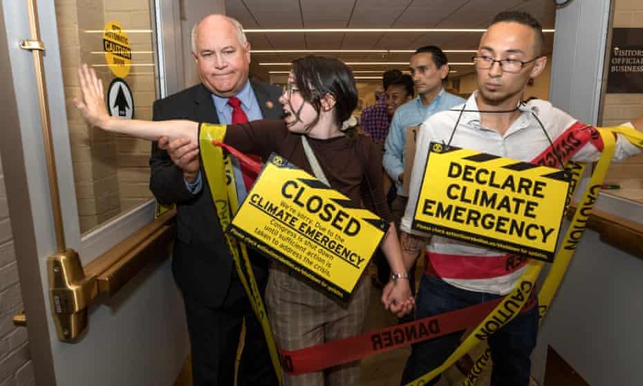 Congressman Ron Estes attempts to pass protestors inside the US Capitol.