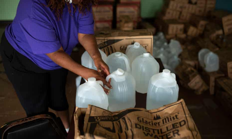 A volunteer prepares gallons of water to be distributed to residents at the Harbor Harvest Urban Ministries in Benton Harbor Michigan.