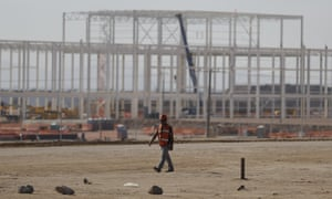 A man walks past the nearly deserted construction site after Ford announced the cancellation of plans to build a $1.6bn plant at San Luis Potosi, Mexico.