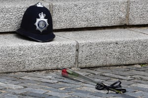 A single red rose is placed in front of Keith Palmer's police helmet at the spot at which he was killed in the Westminster terrorist attack