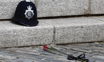 A red rose beside the police helmet of PC Keith Palmer on the day of his funeral on 10 April 2017, close to the spot where he was killed.