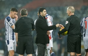 Mikel Arteta, manager of Arsenal, bumps fists with referee Martin Atkinson.