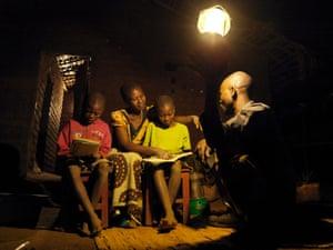 Emily Kamwendo and her husband help their children do homework by the light of solar powered lantern