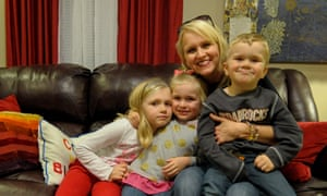Jennifer Baker, center, poses in her home with her children (L-R) Juliette, seven, Emily, four, and Baer, three.
