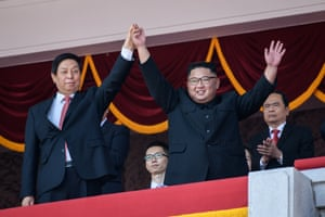 North Korea's leader, Kim Jong-un, waves with China's parliamentary head, Li Zhanshu, from a balcony of the Grand People's Study House on Kim Il-sung Square