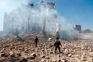 Rebel fighters inspect the damage after a reported air strike carried out by the Saudi-led coalition targeted the presidential palace in the Yemeni capital Sanaa.