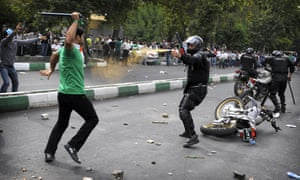 An Iranian riot-police officer sprays teargas at a protester who is attacking him with a police baton, during riots in Tehran in June 2009.