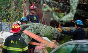 Firefighters work to remove a tree that fell on a house during Hurricane Florence in Wilmington, North Carolina on Friday.