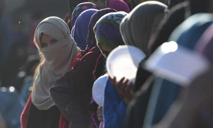 Iraqi women and children queue for food in a refugee camp